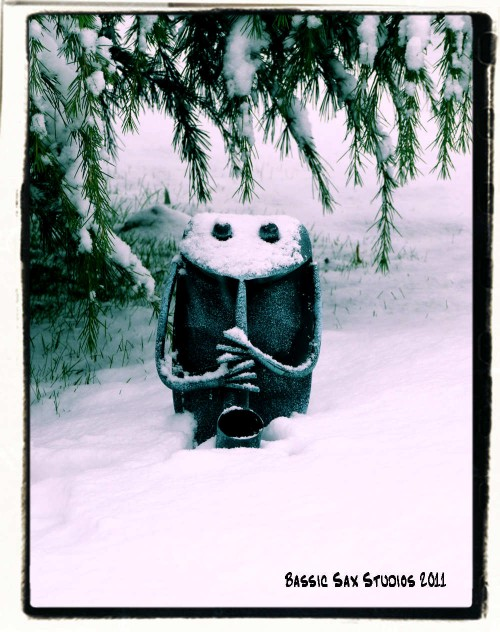 frog playing saxophone garden ornament in the snow under pine tree