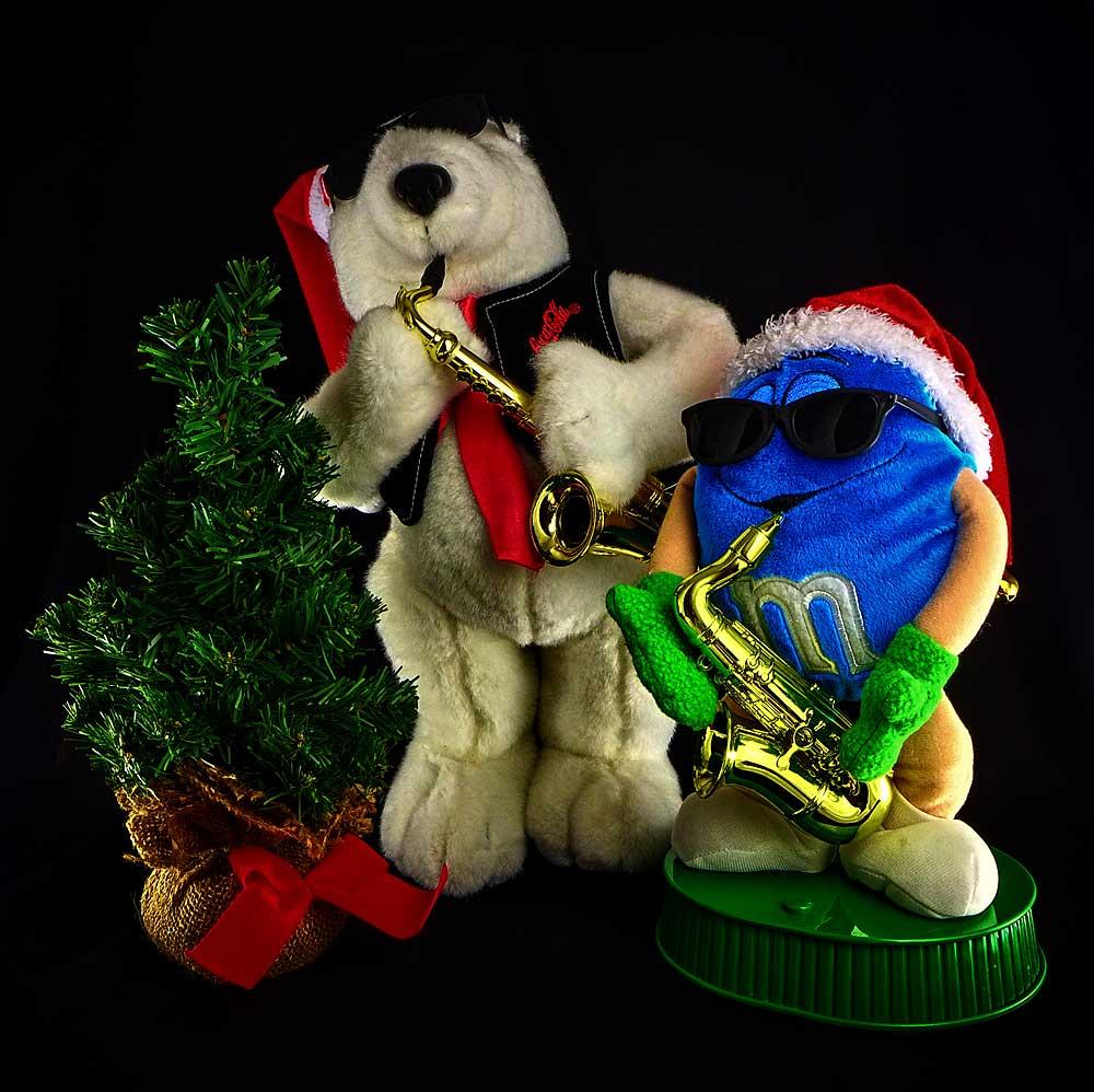 animiated blue M&M guy playing sax, animiated Coca Cola bear playing sax, Christmas tree, animated Christmas figures playing sax