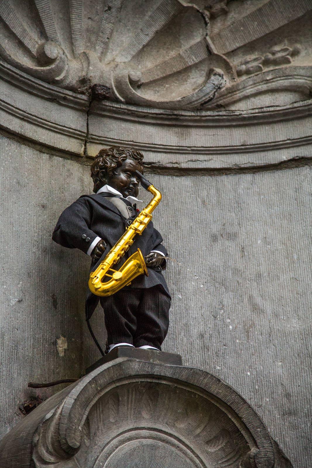 Manneken Pis, Brussels, Belgium, toy saxophone, commemoration of Adolphe Sax, piss on it