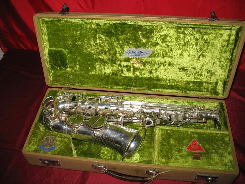 alto saxophone, sax case, G.H. Hüller, green velvet case interior, red cloth background